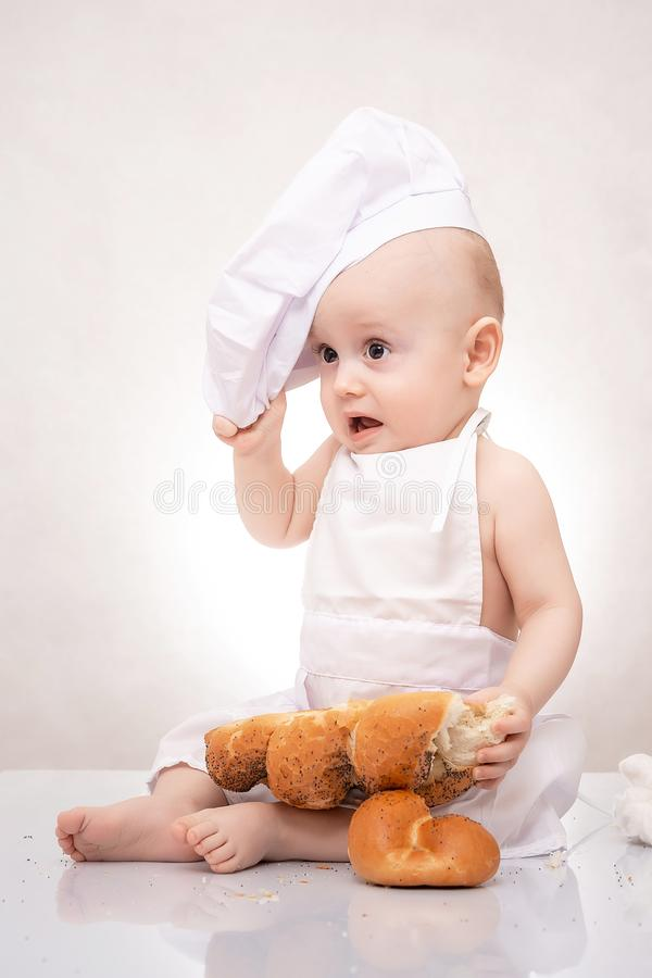 Αστείο μικρό παιδί στο κοστούμι μαγείρων με το ψωμί στοκ εικόνα με δικαίωμα ελεύθερης χρήσης