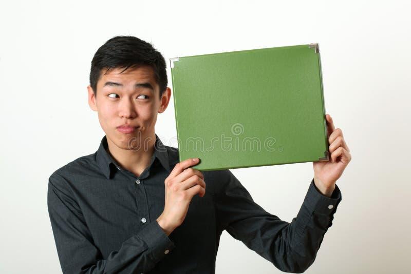 Αστείο νέο ασιατικό άτομο που παρουσιάζει στο πράσινο αντίγραφο διαστημικό κιβώτιο και που φαίνεται το s στοκ εικόνες
