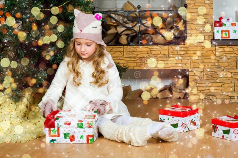 Αστείο ξανθό κορίτσι μικρών παιδιών που περιμένει την έκπληξη από το δώρο παρόν στοκ εικόνα