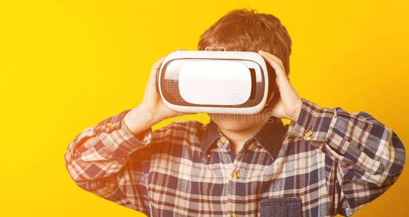 Αστείο παίζοντας παιχνίδι αγοριών στα γυαλιά εικονικής πραγματικότητας Κινηματογράφοι προσοχής παιδιών ή παίζοντας τηλεοπτικά παι στοκ εικόνες