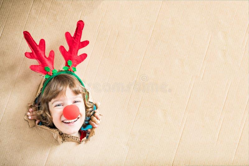 Αστείο παιδί που κοιτάζει μέσω της τρύπας στο χαρτόνι στοκ εικόνες