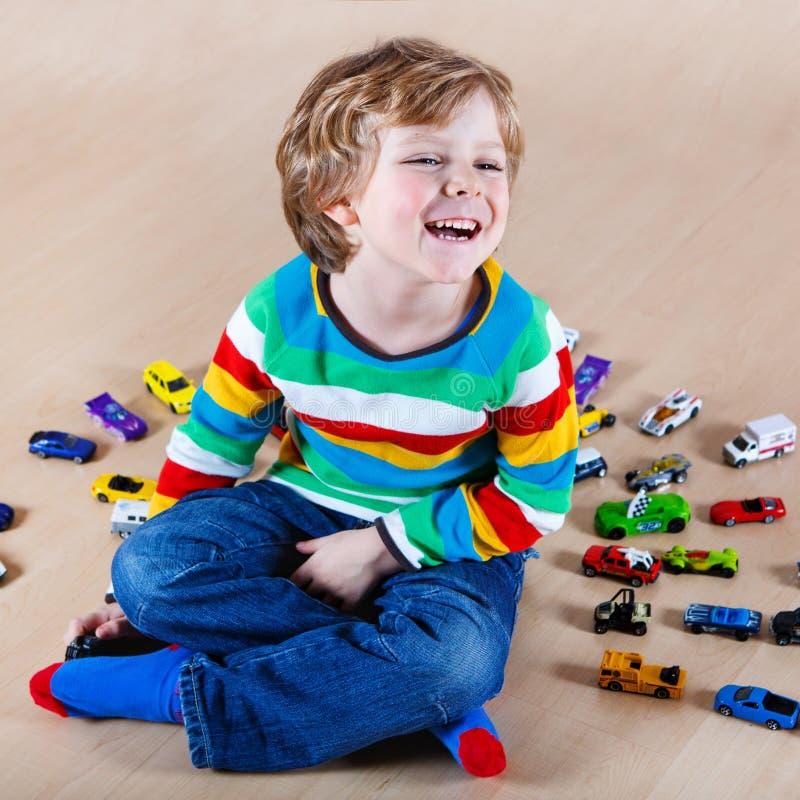 Αστείο παιχνίδι παιδάκι με τα μέρη των αυτοκινήτων παιχνιδιών εσωτερικών στοκ φωτογραφίες με δικαίωμα ελεύθερης χρήσης