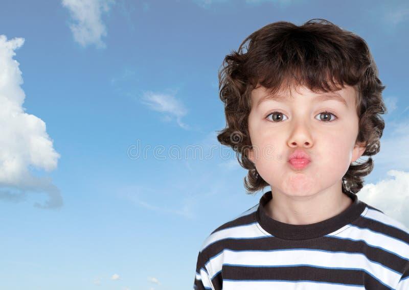 Αστείο παιδί που κάνει το μορφασμό που ρίχνει ένα φιλί στοκ φωτογραφία