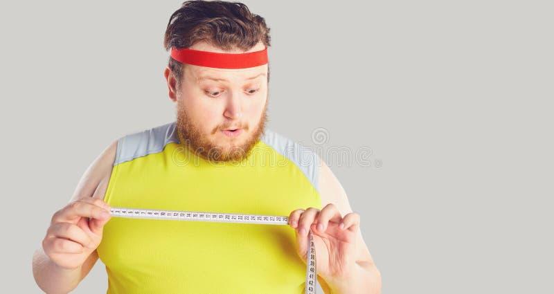 Αστείο παχύ άτομο με μια γενειάδα που κρατά ένα εκατοστόμετρο στα χέρια του με την αστεία συγκίνηση στοκ εικόνες
