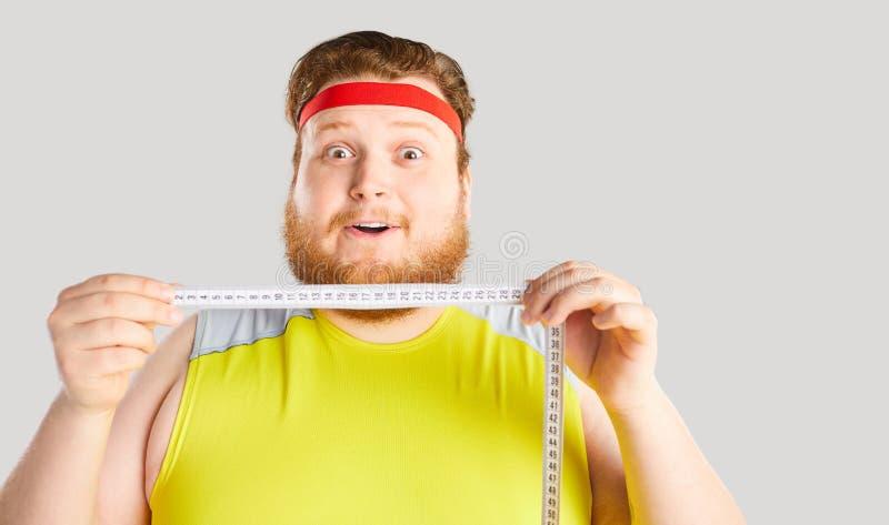 Αστείο παχύ άτομο που κρατά ένα εκατοστόμετρο με την αστεία συγκίνηση στοκ φωτογραφία με δικαίωμα ελεύθερης χρήσης