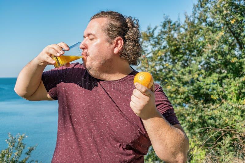 Αστείο παχύ άτομο στον ωκεάνιο χυμό κατανάλωσης και κατανάλωση των φρούτων Διακοπές, απώλεια βάρους και υγιής κατανάλωση στοκ φωτογραφία με δικαίωμα ελεύθερης χρήσης