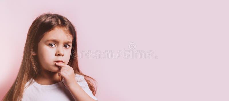 Αστείο πορτρέτο λίγου κοριτσιού αμφιβολίας στο ρόδινο υπόβαθρο στοκ εικόνες