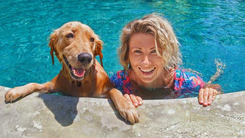 Αστείο πορτρέτο της γυναίκας smiley με το σκυλί στην πισίνα στοκ φωτογραφία