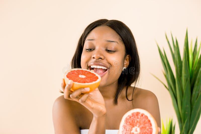 Αστείο πορτρέτο της νέας γυναίκας αφροαμερικάνων με το γκρέιπφρουτ στο άσπρο υπόβαθρο στοκ εικόνα με δικαίωμα ελεύθερης χρήσης