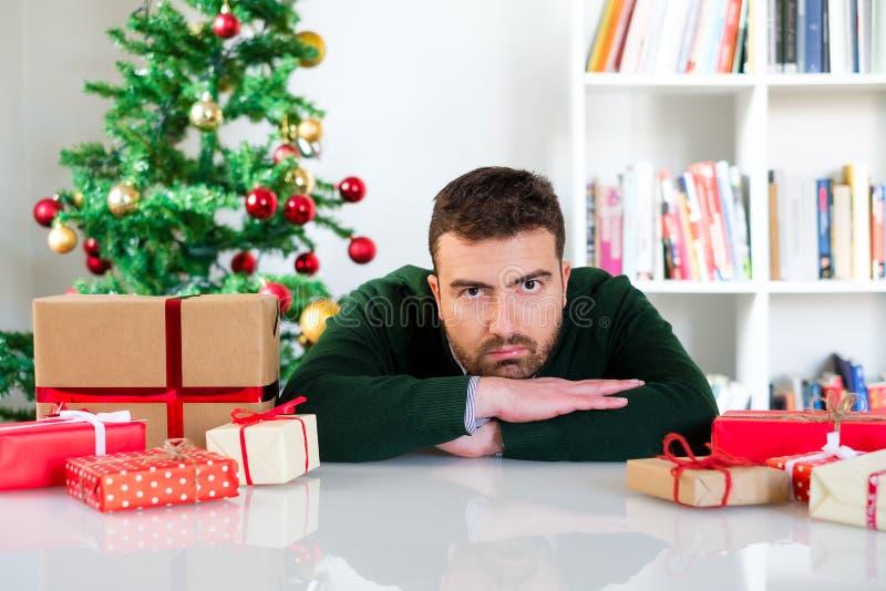 Αστείο πρόσωπο ενός ατόμου που απογοητεύεται μέχρι τα χριστουγεννιάτικα δώρα στοκ εικόνες