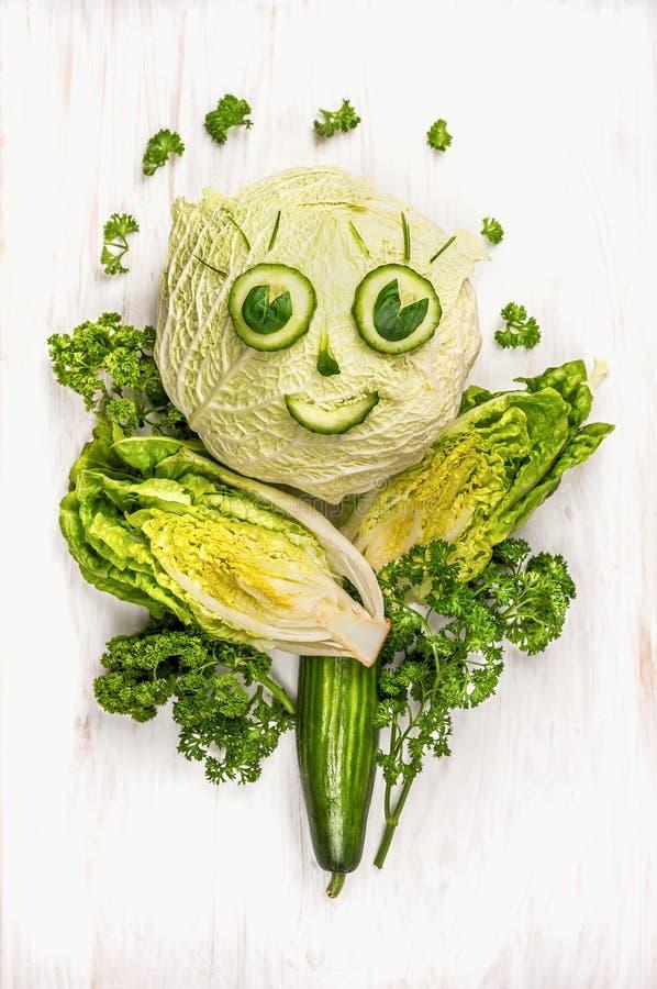 Αστείο πρόσωπο κοριτσιών φιαγμένο από πράσινα λαχανικά, αγγούρι και μαρούλι άσπρο σε ξύλινο στοκ φωτογραφία με δικαίωμα ελεύθερης χρήσης