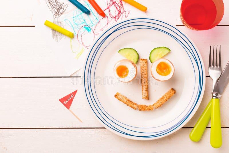 Αστείο πρόσωπο - πρόγευμα του παιδιού - αυγά, φρυγανιές και αγγούρι στοκ φωτογραφίες με δικαίωμα ελεύθερης χρήσης
