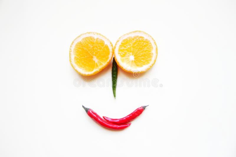 αστείο πρόσωπο φιαγμένο από φρούτα και λαχανικά δύο στρογγυλά πορτοκάλια που τεμαχίζονται, κόκκινα και πράσινα πιπέρια σε ένα ελα στοκ εικόνα