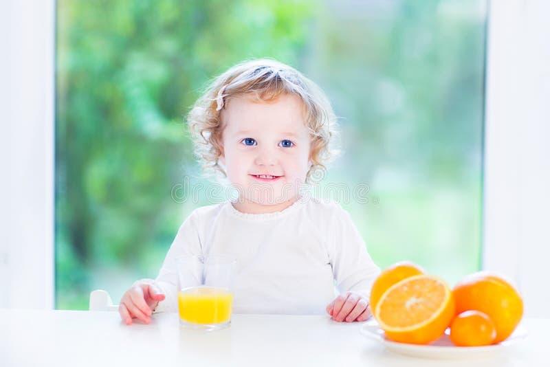 Αστείο σγουρό κορίτσι μικρών παιδιών που πίνει το χυμό από πορτοκάλι στοκ φωτογραφία