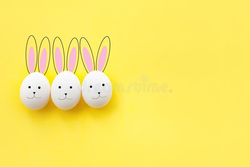 Αστείο συρμένο λαγουδάκι τρία από τα αυγά κοτόπουλου σε ένα κίτρινο υπ στοκ εικόνα με δικαίωμα ελεύθερης χρήσης