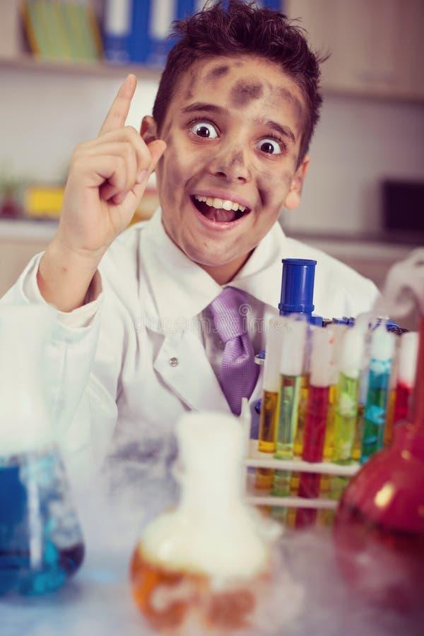 Αστείο τρελλό αγόρι επιστημόνων που εργάζεται σε ένα εργαστήριο στοκ εικόνες