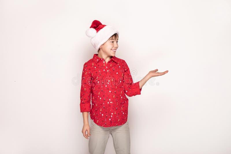 Αστείο χαμογελώντας αγόρι παιδιών στο κόκκινο καπέλο Santa στοκ φωτογραφία με δικαίωμα ελεύθερης χρήσης
