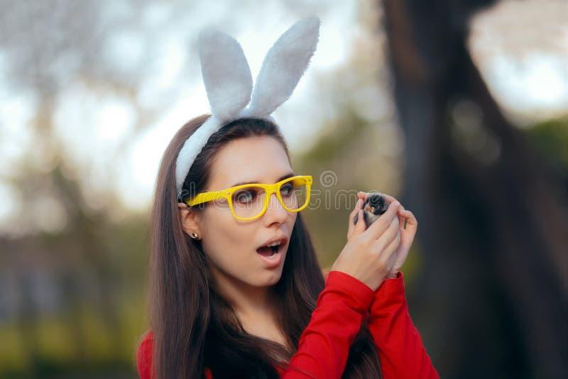 Αστείο χαριτωμένο κορίτσι με τα αυτιά λαγουδάκι με το νεοσσό Πάσχας στοκ εικόνες