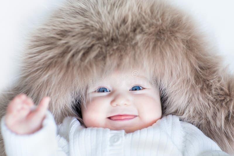 Αστείο χαριτωμένο κοριτσάκι που φορά το τεράστιο χειμερινό καπέλο στοκ εικόνες
