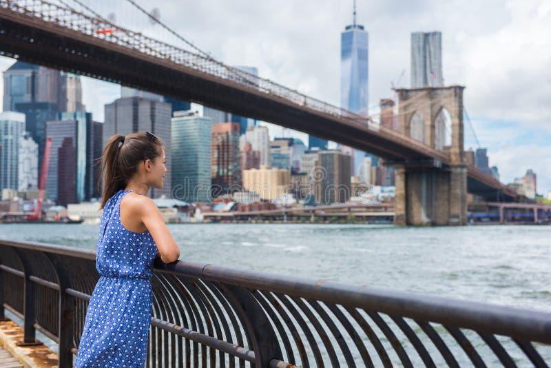 Αστική γυναίκα τουριστών πόλεων της Νέας Υόρκης που εξετάζει τη γέφυρα του Μπρούκλιν και τον ορίζοντα στοκ φωτογραφίες