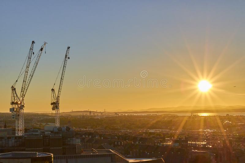 Αστική εικονική παράσταση πόλης με τους γερανούς ηλιοβασίλεμα με τις ακτίνες ήλιων, Εδιμβούργο, Σκωτία, Ηνωμένο Βασίλειο στοκ εικόνα