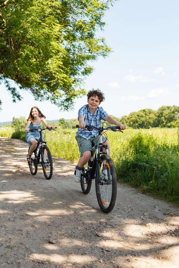 Αστικό - παιδιά που οδηγούν τα ποδήλατα στοκ εικόνες