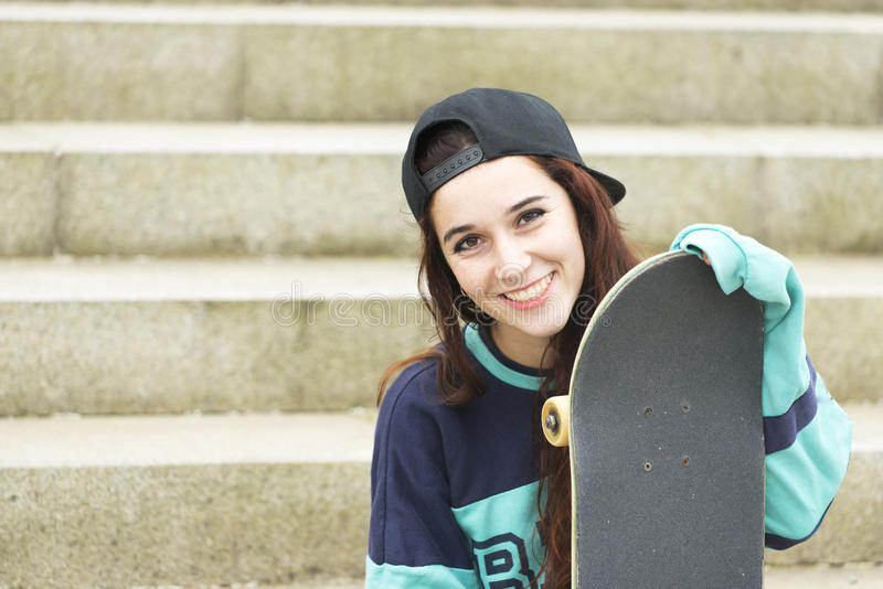 Αστικό πορτρέτο της εύθυμης νέας γυναίκας με skateboard στοκ εικόνα