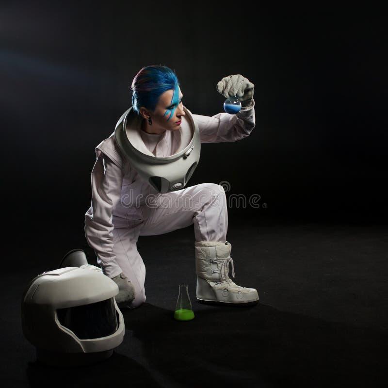 Αστροναύτης σε ένα μαύρο υπόβαθρο, μια νέα γυναίκα με την τέχνη προσώπου στο διαστημικό κοστούμι στοκ φωτογραφία