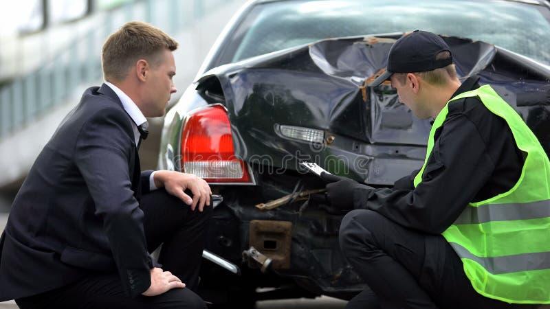 Αστυνομικός επιθεωρητής που συμπληρώνει την αναφορά για τροχαίο ατύχημα, αναλύοντας τις ζημιές, αγχωμένος οδηγός στοκ φωτογραφία με δικαίωμα ελεύθερης χρήσης