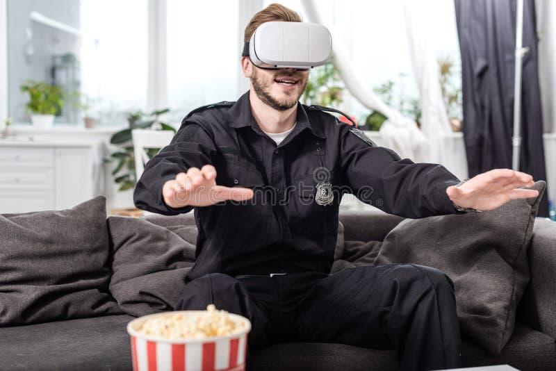 αστυνομικός με την κάσκα εικονικής πραγματικότητας στην επικεφαλής συνεδρίαση στον καναπέ και στοκ φωτογραφίες