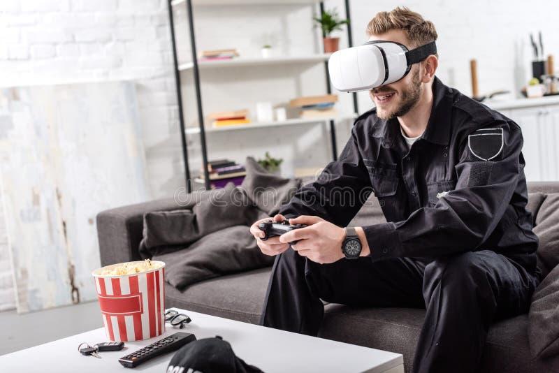αστυνομικός με την κάσκα εικονικής πραγματικότητας στην επικεφαλής εκμετάλλευση gamepad, τη συνεδρίαση στον καναπέ και στοκ εικόνες με δικαίωμα ελεύθερης χρήσης