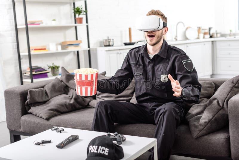 αστυνομικός με την κάσκα εικονικής πραγματικότητας στον επικεφαλής popcorn εκμετάλλευσης κάδο και τη συνεδρίαση στοκ φωτογραφία με δικαίωμα ελεύθερης χρήσης