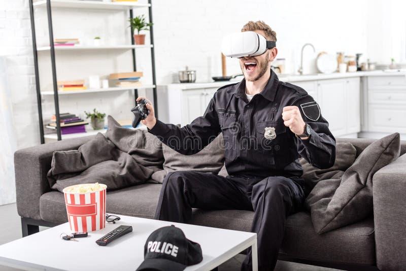 αστυνομικός με την κάσκα εικονικής πραγματικότητας στο επικεφαλής παίζοντας τηλεοπτικό παιχνίδι και κραυγή με τη χαρά στοκ φωτογραφίες με δικαίωμα ελεύθερης χρήσης