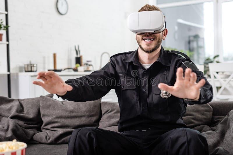 αστυνομικός με την κάσκα εικονικής πραγματικότητας στο επικεφαλής παίζοντας τηλεοπτικό παιχνίδι στοκ φωτογραφία