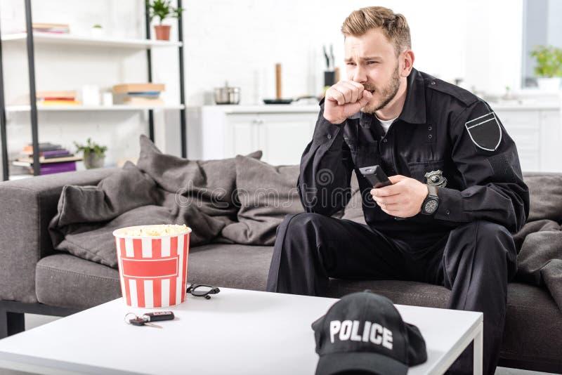 αστυνομικός με τη φοβησμένη συνεδρίαση έκφρασης προσώπου στον καναπέ και στοκ φωτογραφία με δικαίωμα ελεύθερης χρήσης