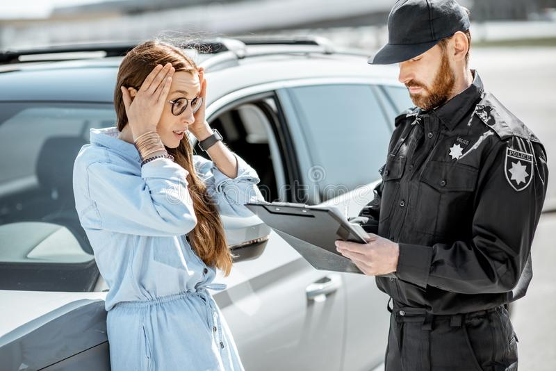 Αστυνομικός με το θηλυκό οδηγό στην άκρη του δρόμου στοκ εικόνες