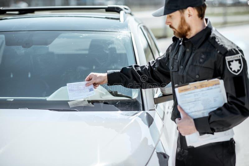 Αστυνομικός που βάζει το πρόστιμο στο αυτοκίνητο στοκ εικόνες