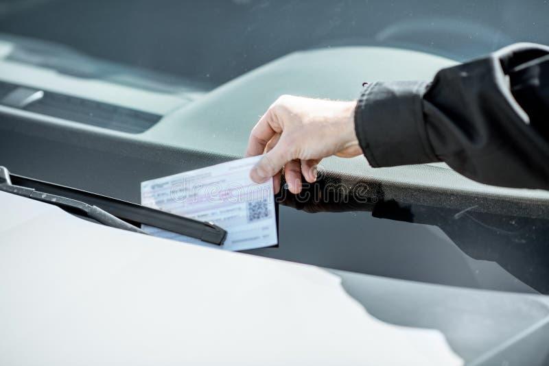 Αστυνομικός που βάζει το πρόστιμο στο αυτοκίνητο στοκ εικόνα