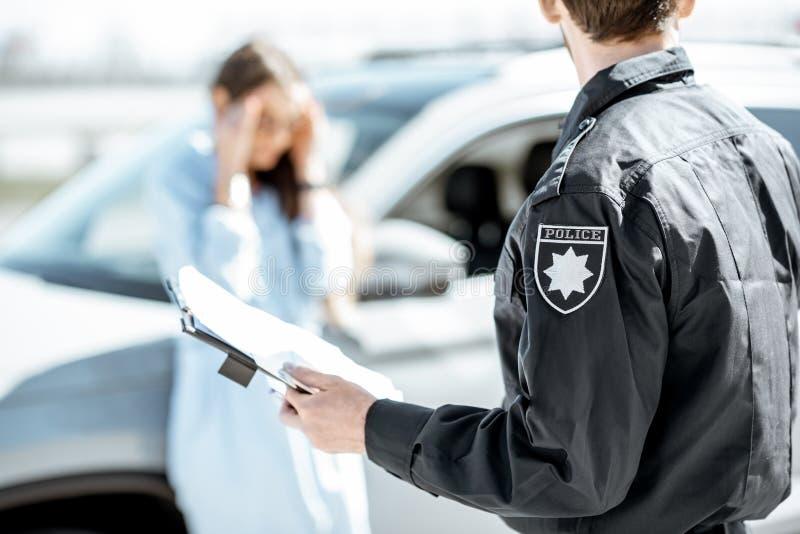 Αστυνομικός που εκδίδει ένα πρόστιμο για έναν οδηγό γυναικών στοκ φωτογραφία με δικαίωμα ελεύθερης χρήσης