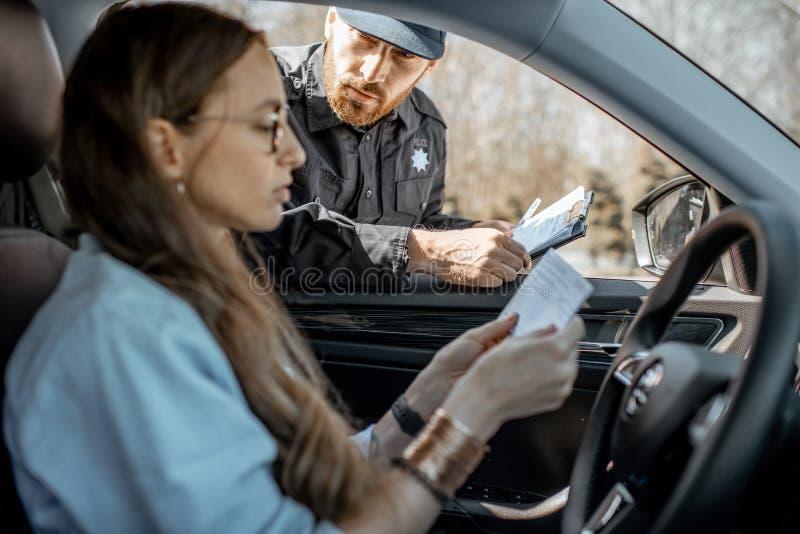 Αστυνομικός που ελέγχει τα έγγραφα ενός θηλυκού οδηγού στοκ εικόνες με δικαίωμα ελεύθερης χρήσης