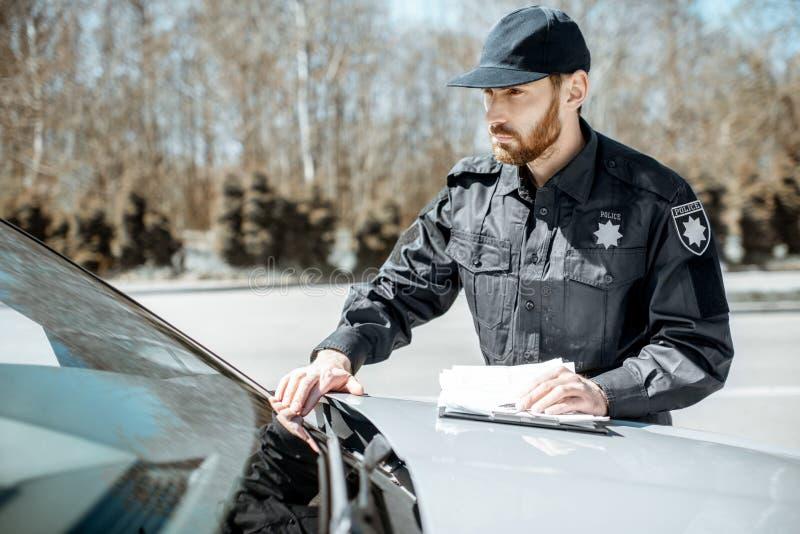 Αστυνομικός που ελέγχει τον αριθμό αυτοκινήτων στοκ φωτογραφίες