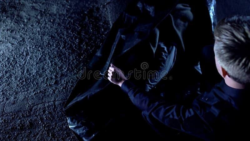 Αστυνομικός που κλείνει τη μαύρη σακούλα για μεταφορά πτωμάτων με το πτώμα του θύματος, σκληρή δολοφονία στην οδό στοκ φωτογραφίες με δικαίωμα ελεύθερης χρήσης