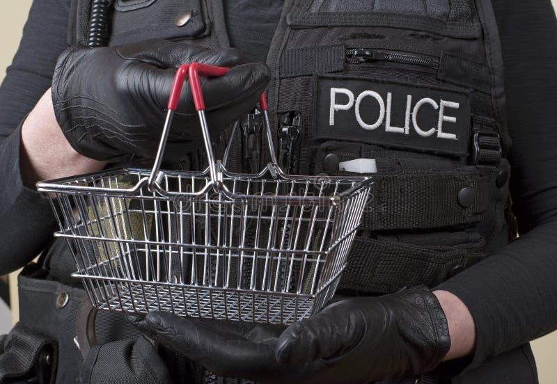Αστυνομικός που κρατά το μικρό καλάθι καλωδίων στοκ φωτογραφία