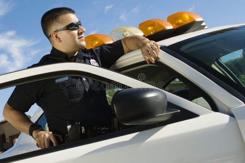 Αστυνομικός που κλίνει στο περιπολικό αυτοκίνητο στοκ φωτογραφία