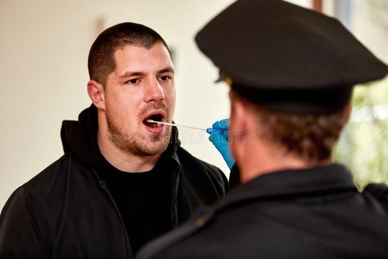 Αστυνομικός που παίρνει το δείγμα σαλίου ως δοκιμή DNA στοκ φωτογραφία με δικαίωμα ελεύθερης χρήσης