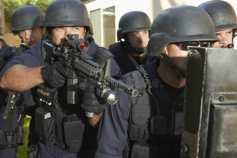 Αστυνομικός που στοχεύει στεμένος με τους συναδέλφους στοκ φωτογραφία με δικαίωμα ελεύθερης χρήσης