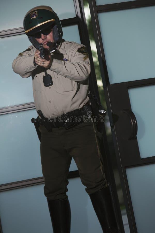 Αστυνομικός που στοχεύει το περίστροφο ενάντια στην πόρτα στοκ εικόνα