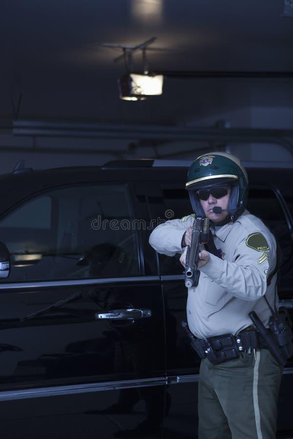 Αστυνομικός που στοχεύει το περίστροφο στεμένος μπροστά από το αυτοκίνητο στοκ φωτογραφία με δικαίωμα ελεύθερης χρήσης