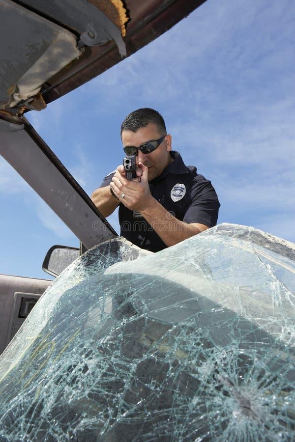 Αστυνομικός που στοχεύει το πυροβόλο όπλο μέσω του σπασμένου ανεμοφράκτη στοκ εικόνα