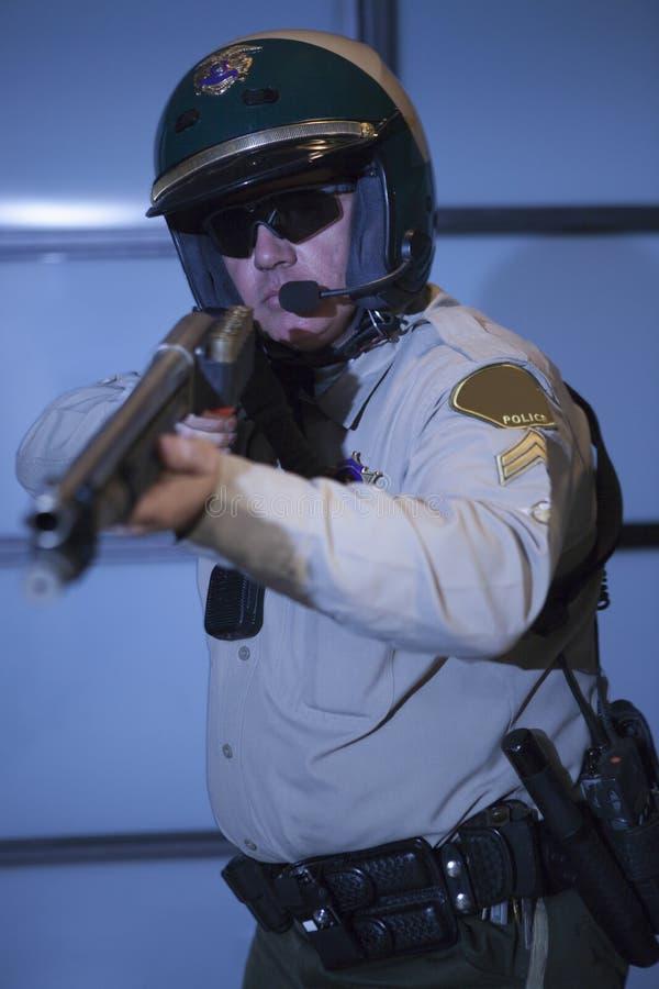 Αστυνομικός που στοχεύει το τουφέκι ενάντια στην πόρτα στοκ εικόνες με δικαίωμα ελεύθερης χρήσης